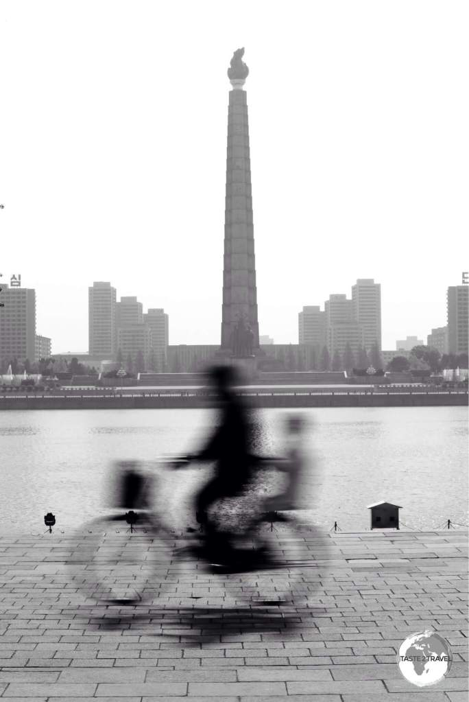 A cyclist passing in front of Juche tower.