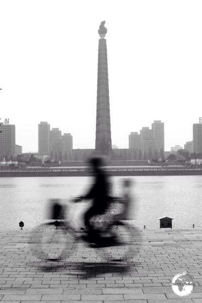 A cyclist on Kim Il-sung square, passing in front of Juche tower.