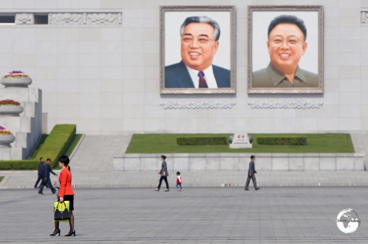 A cyclist passes in front of images of the former leaders, Kim Il-Sung and Kim Jong-Il which overlook Kim Il-Sung square.