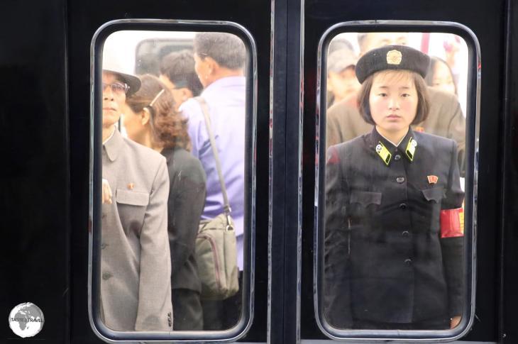 A Pyongyang metro guard, standing at attention, on a departing train at Yonggwang metro station.
