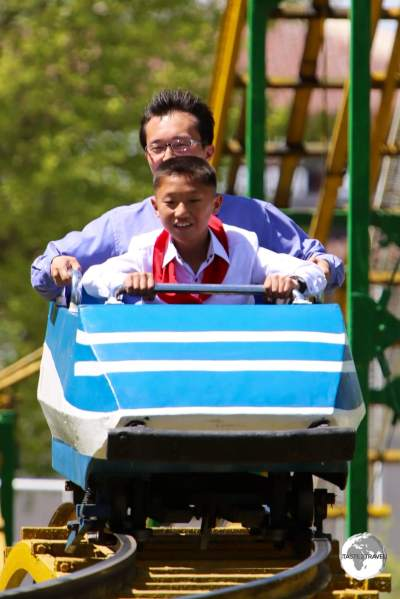 A father and son enjoying a roller coaster ride at Taesongsan Fun Fair on a busy May day public holiday.