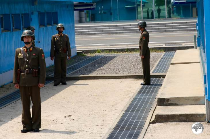 The low concrete ridge running between the huts marks the border between North and South Korea.
