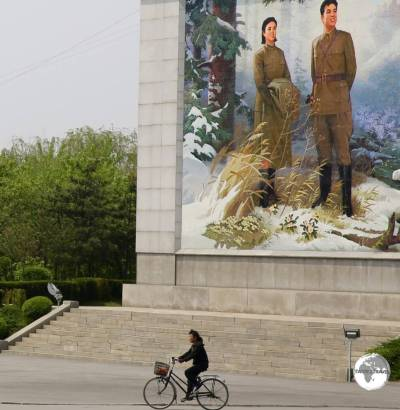A cyclist in Nampo passes in front of a giant propaganda image.