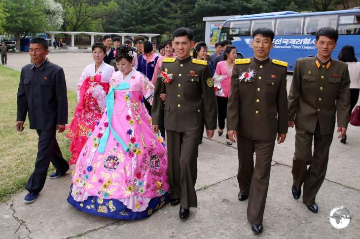 As required, newlyweds arrive at a park near Pyongyang to pay their respects at a statue of Kim Il-Sung.