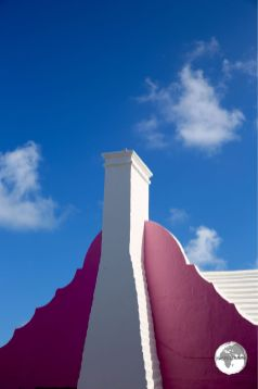 A white chimney and pink gable contrast against a clear blue sky in St. Georges town.
