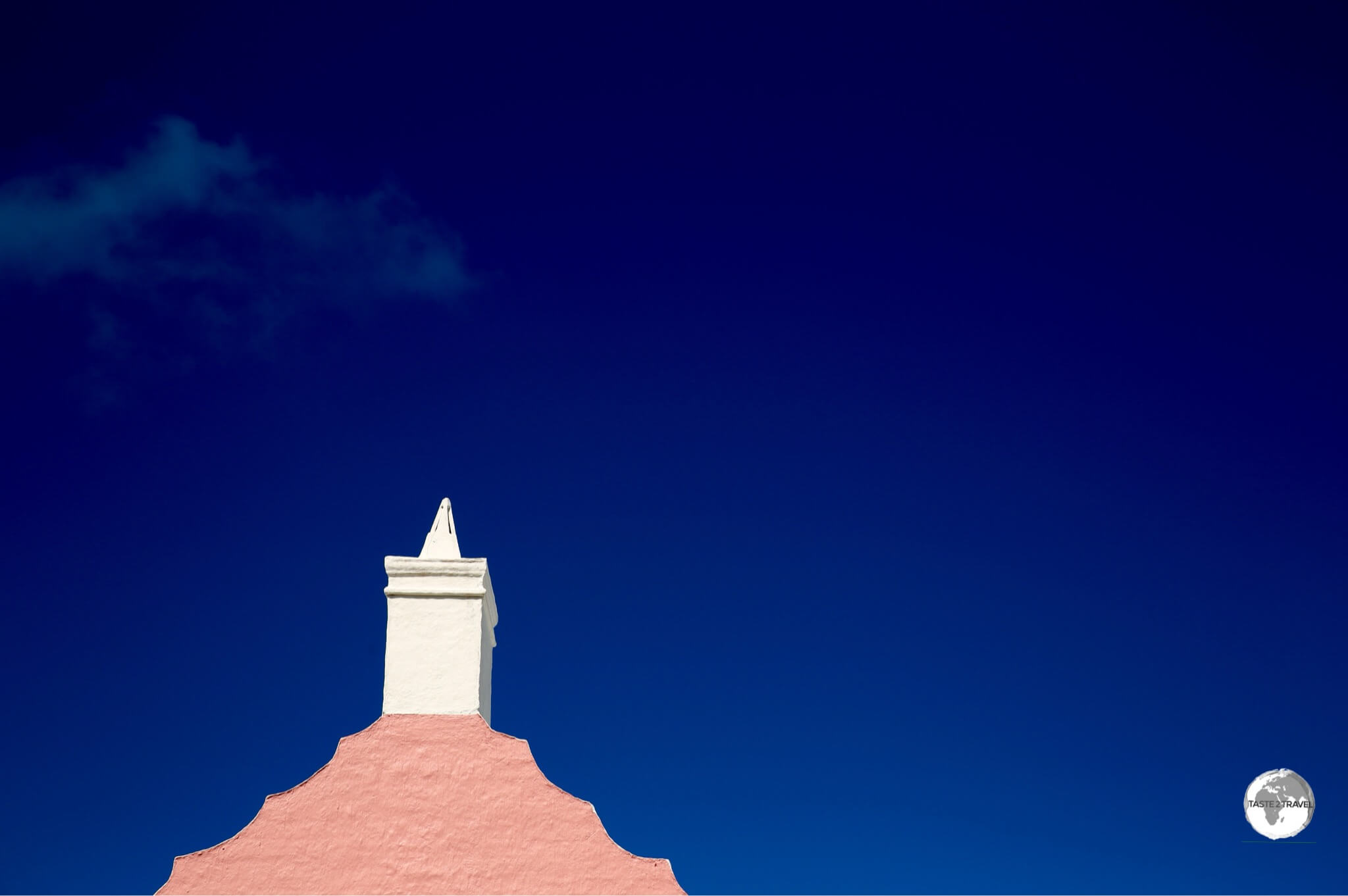 A pink gable and white chimney contrast nicely against the blue Bermuda sky.
