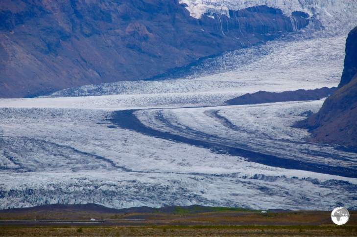 Cars passing in front of Skaftafellsjökull provide a sense of scale.