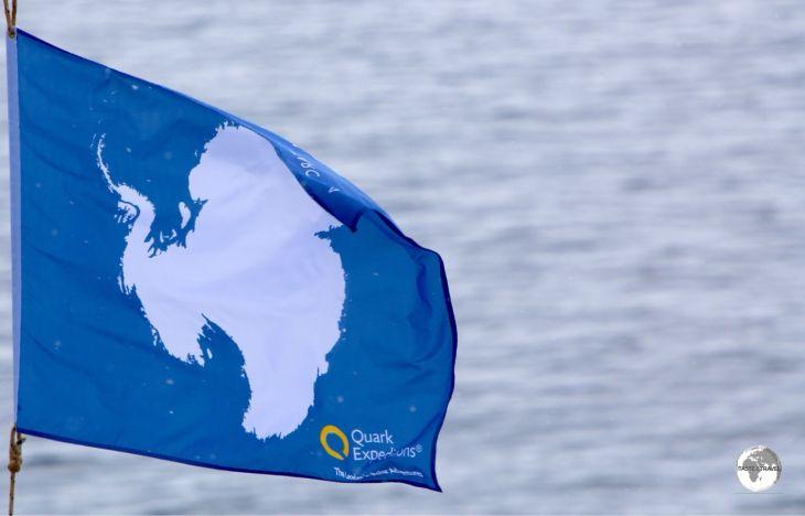 The flag of Antarctica flies on the bow of the Ocean Diamond.