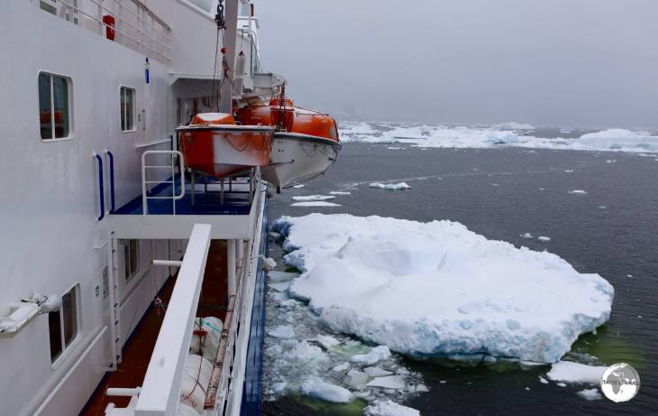 The <i>Ocean Diamond</i>, moored against a large chunk of ice, on a stormy day, in the Yalour Islands.