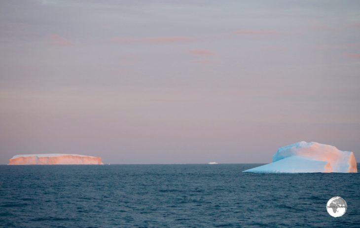 Icebergs glow in the setting Antarctic sun.