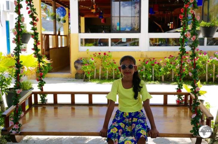 A young girl relaxing on Maafushi Island.