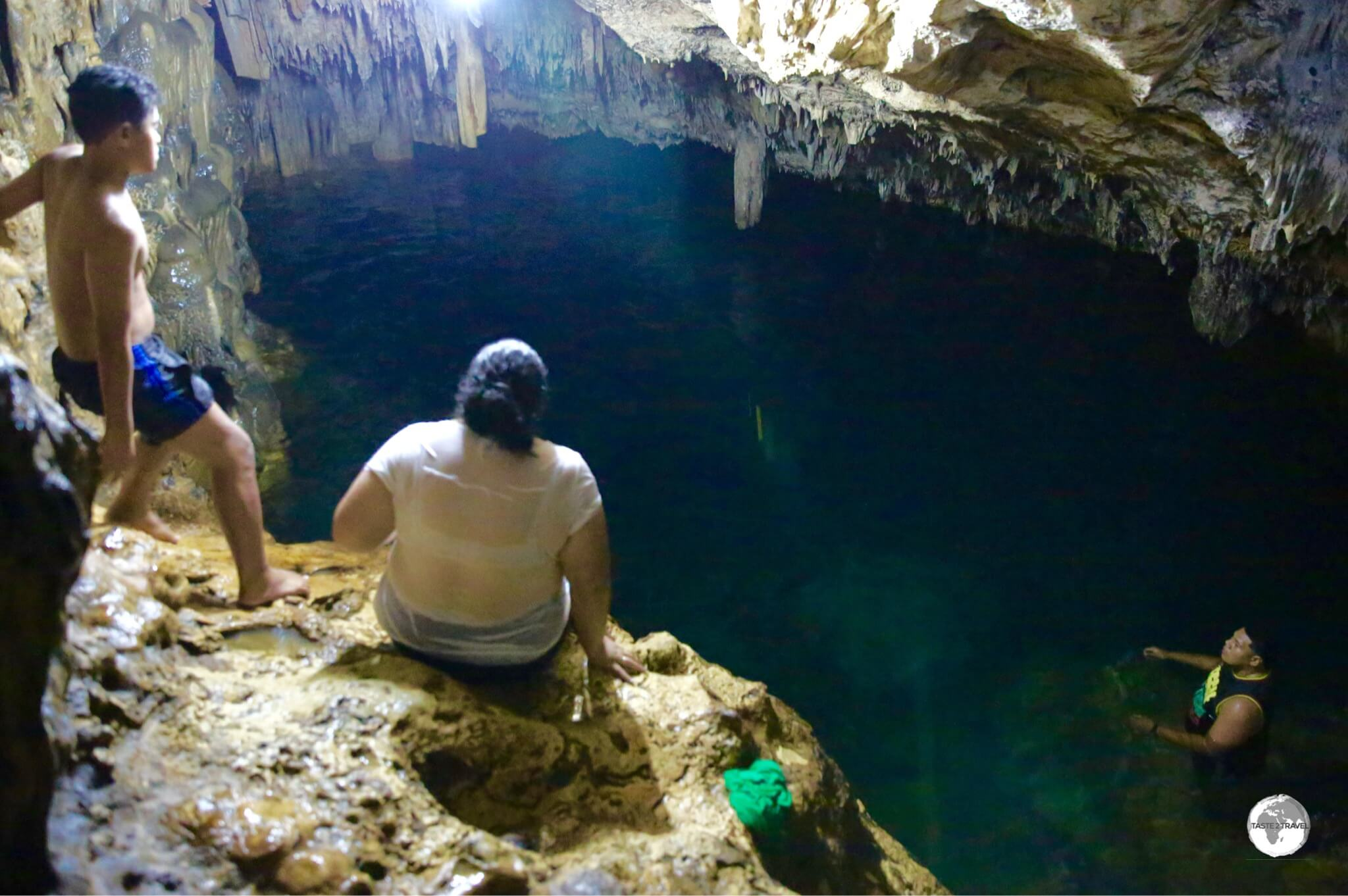 Locals bathing in the deep freshwater pool inside 'Anahulu Cave.