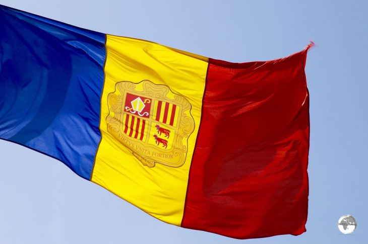 Andorra Travel Guide: The flag of Andorra, a vertical tri-colour of blue, yellow, and red with the coat of arms of Andorra in the centre.