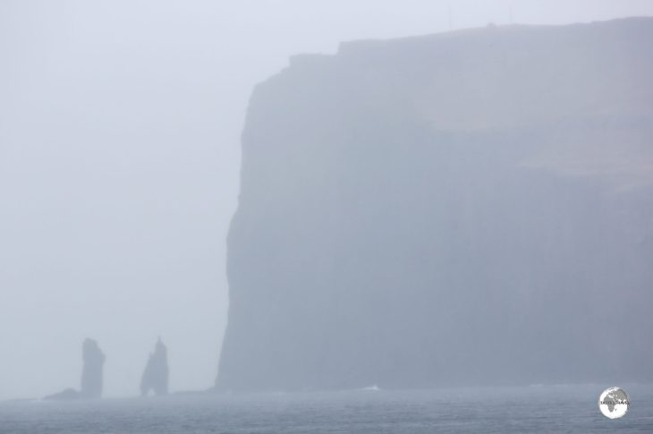 A hazy view of the soaring 343-metre-high Eiðiskollur promontory with the two 75-m high sea stacks - Risin og Kellingin.