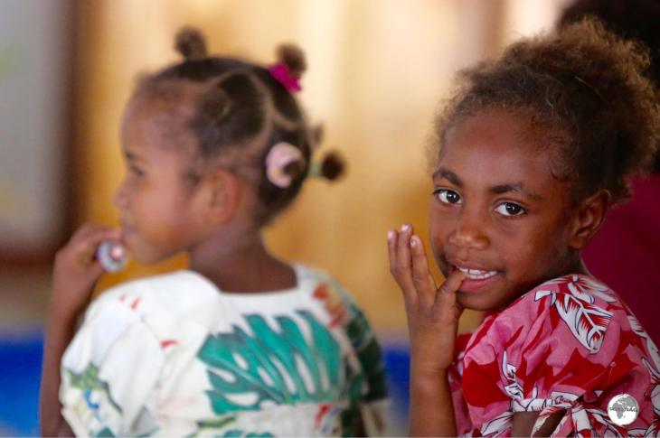 A young girl is distracted during a church service in the village of Louna Sunan.