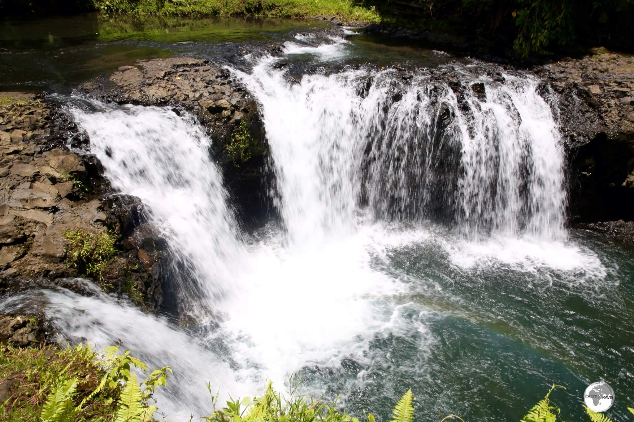 Surrounded by lush vegetation, the Togitogiga Waterfalls are a popular swimming hole.