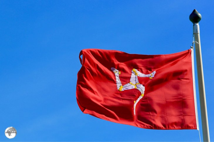 The Isle of Man flag fluttering in the breeze on the promenade in Douglas.