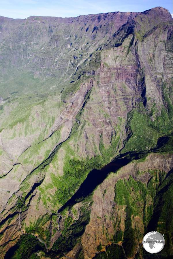 As seen from a helicopter, the narrow, windy road (bottom left corner) which passes beneath the vertical walls of the Cirque de Cilaos, providing access to the tiny hamlet of <i>Îlet à Cordes</i>.