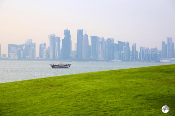 Green grass in the desert and a view of the Doha skyline from MIA park.