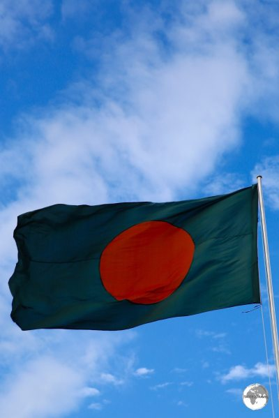 Dhaka Travel Guide: The flag of Bangladesh flying at the Eternal Flame monument.