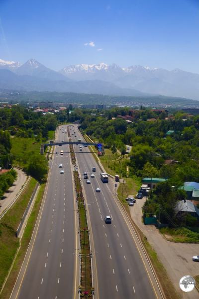A view of a highway in Almaty with the Tien Shan mountains in the background.