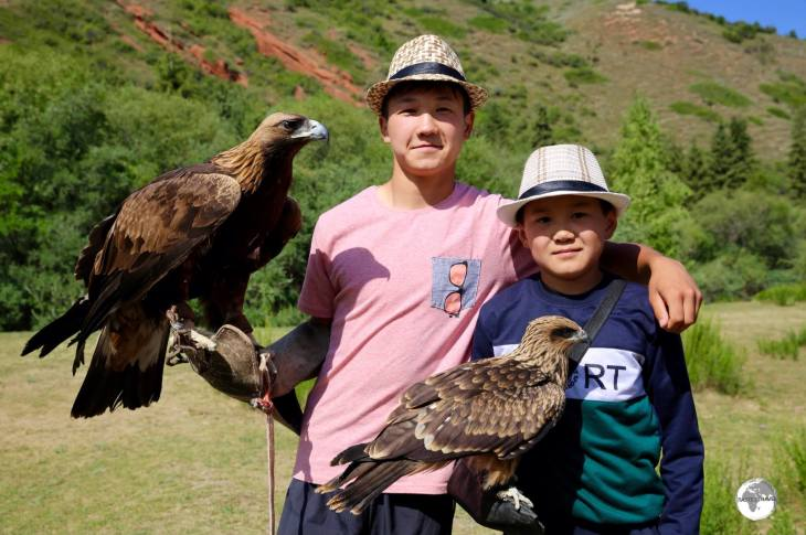 Two young eagle handlers from Jeti-Ögüz, rent their pet raptors out to tourists for the ultimate selfie photo.