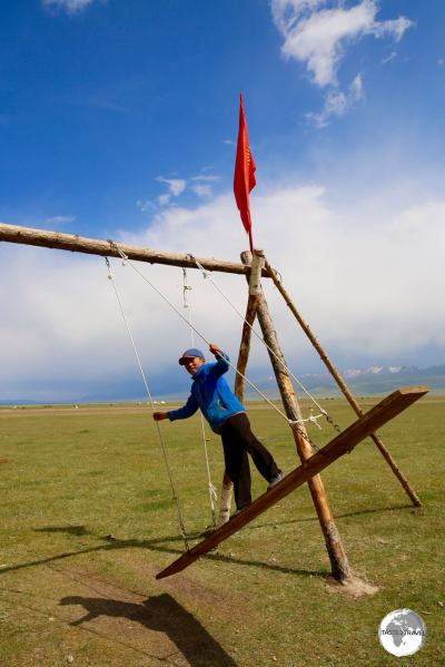 A young boy playing on a traditional Kyrgyz swing on the shore of lake Son-Kul.