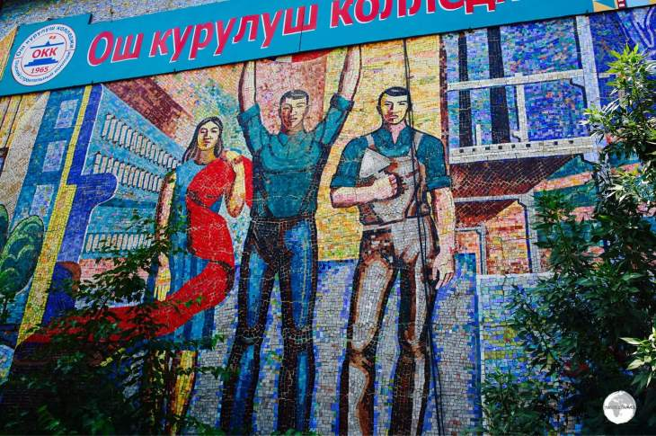 The <b><i>Fabric</i></b> mosaic is installed on the wall of a local technical college and shows three different workers, with one holding a length of red cloth, a symbol of communism.