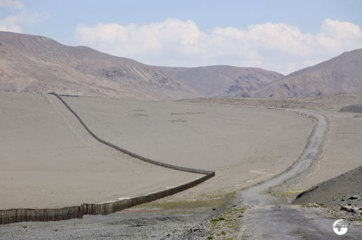 The Pamir highway travels alongside the barbed-wire fence of the Chinese border.