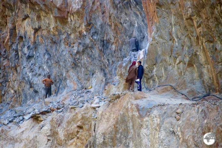 Afghan road workers carving the road out of a cliff face using a single jackhammer.