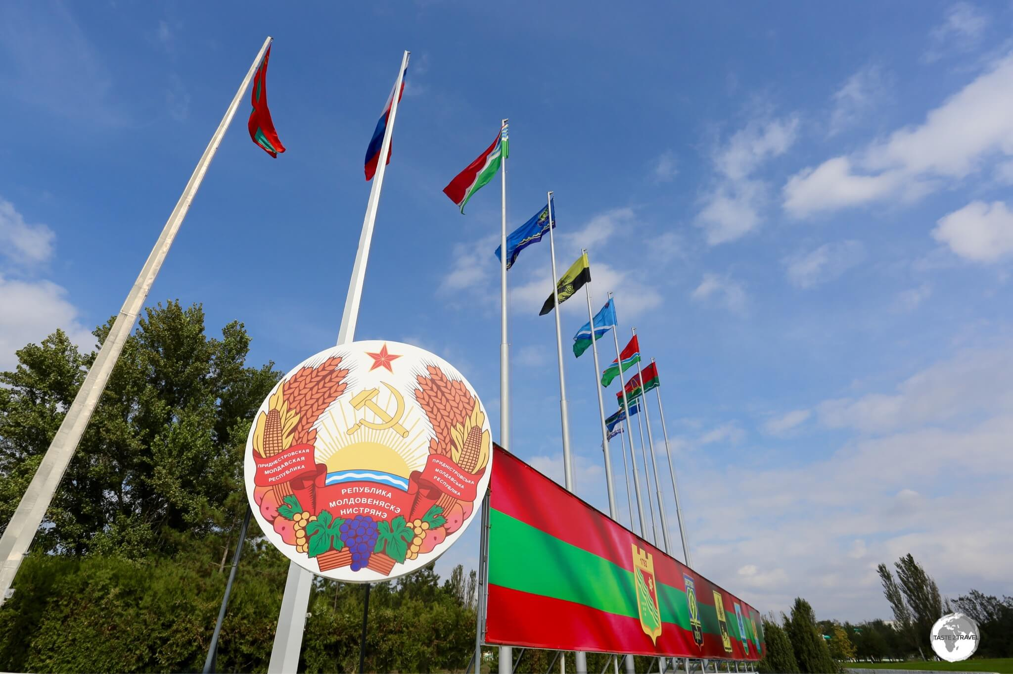 The coat of arms of Transnistria with the flags of (l-r) Transnistria, Russia and the different districts of Transnistria.