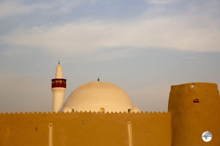 The dome of the Al-Qubba mosque rises above the mud walls of the Ibrahim Palace compound.