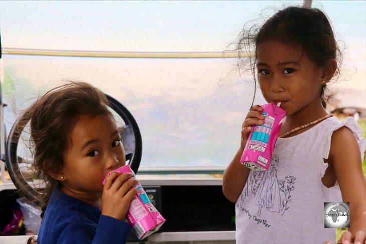 Two Cocos Malay girls, enjoying some strawberry milk, on Home Island.