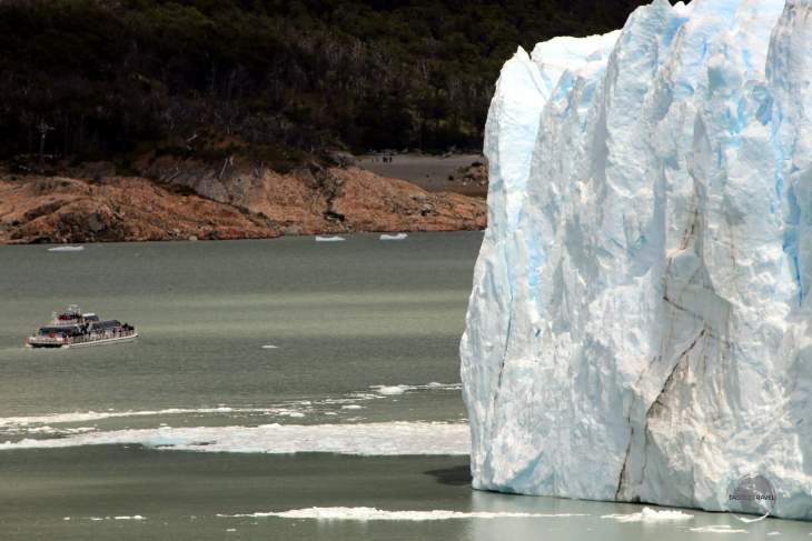 A tour boat on Lago Argentino is dwarfed by the 74 m (240 ft) ice wall of Perito Moreno Glacier in Argentine Patagonia.