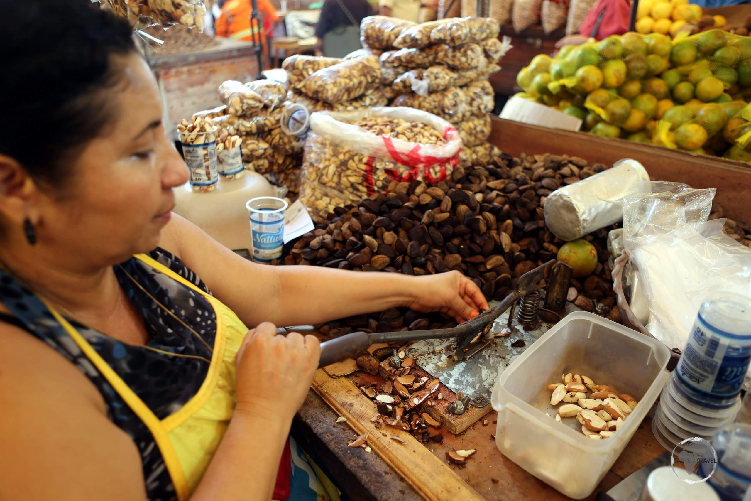A Brazil nut seller in Belém market, using a guillotine to shave the shell off of each nut.
