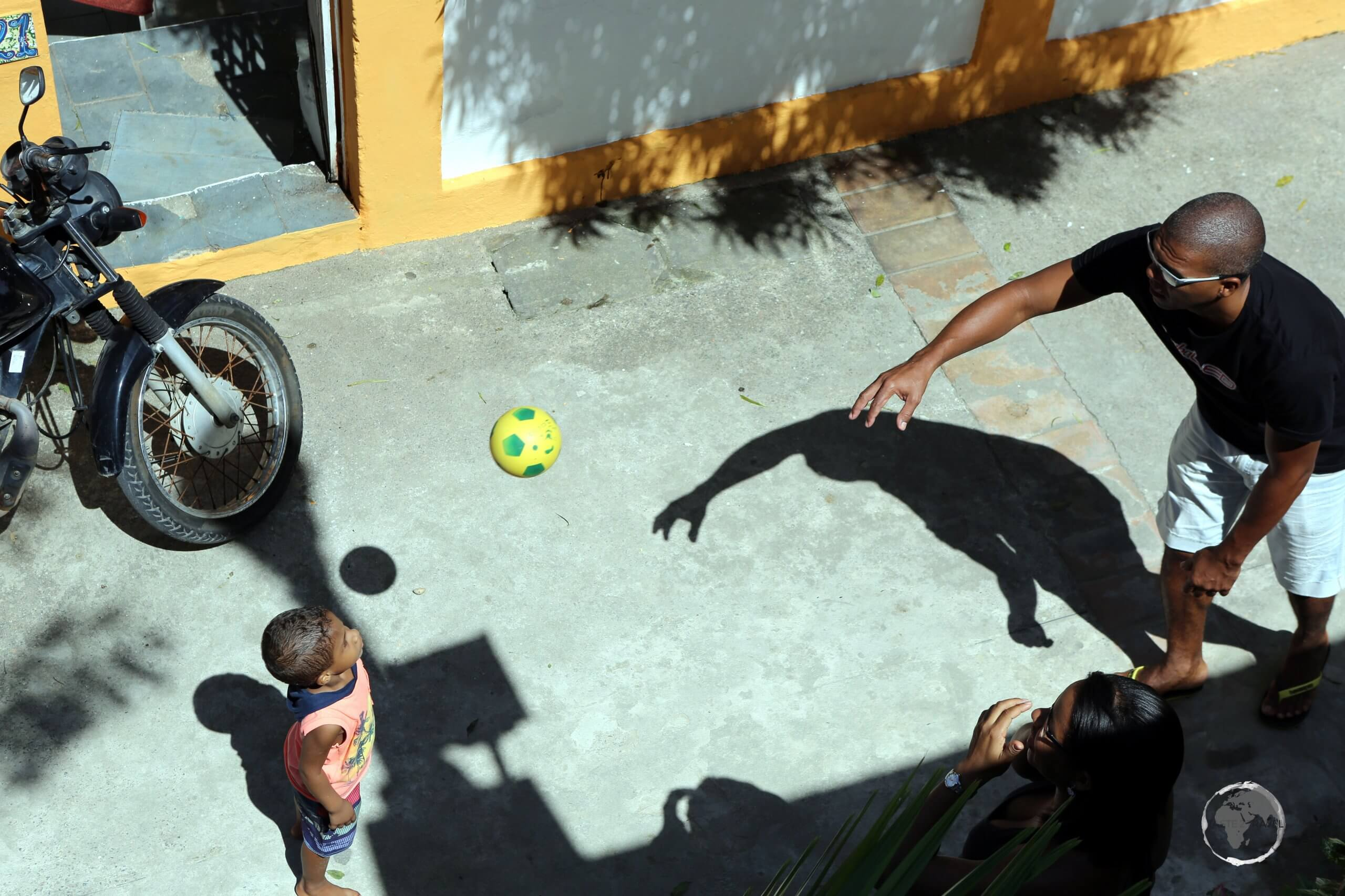 Father and child playing football in Olinda, Pernambuco state, Brazil.