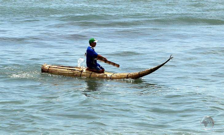 A fisherman at Huanchaco beach, paddling his 'Caballito de Totora' raft, a raft which has existed, unchanged, for more than 3,000 years but is fast disappearing.