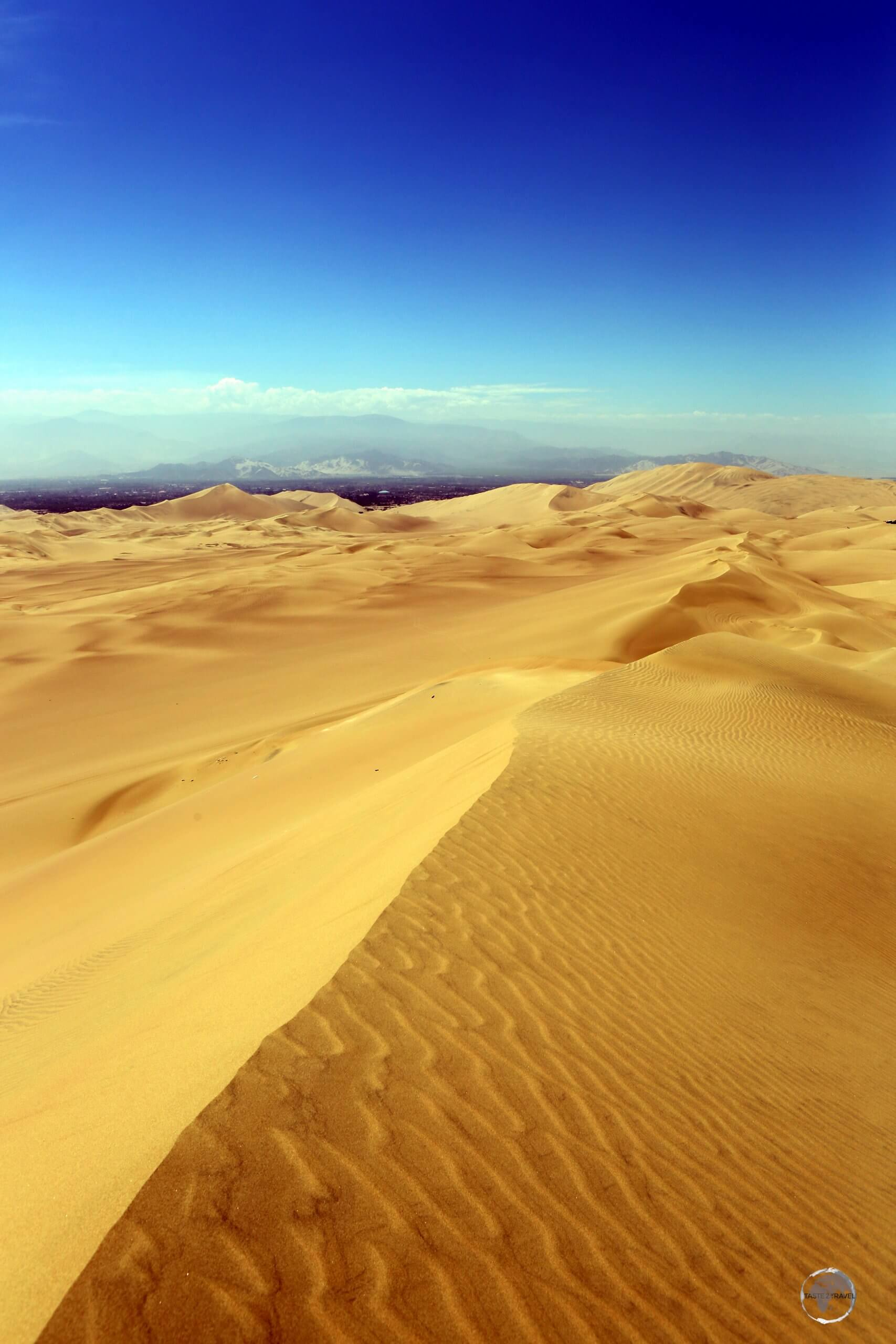 Sand dunes around the Peruvian oasis town of Huacachina, with the foothills of the Andes visible in the background.