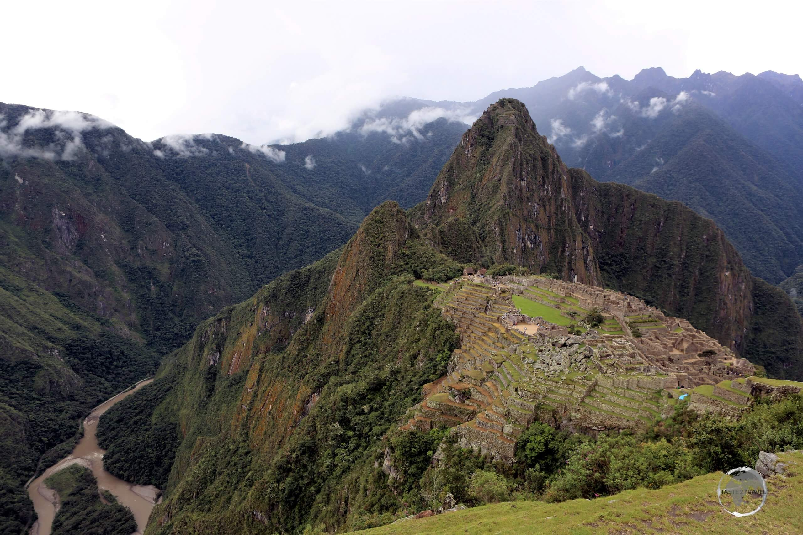 A panoramic view of Machu Picchu, which sits atop a steeply-side ridge, high above the Urubamba River at an elevation of 2,430 metres (7,970 ft).
