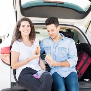 Beautiful young woman sitting in car boot with her boyfriend eating sandwiches, lunch break on road trip