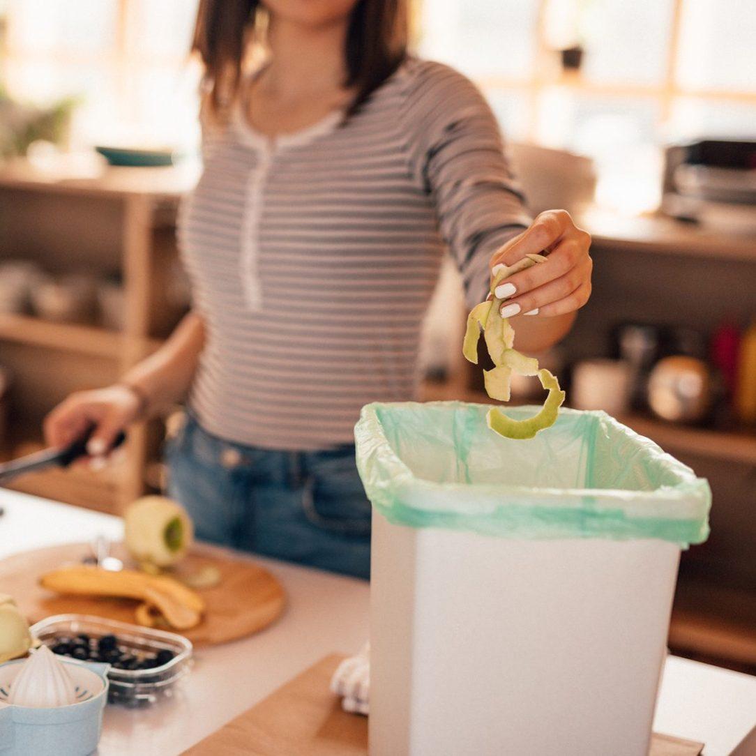 Millennial woman putting organic waste in compost bin