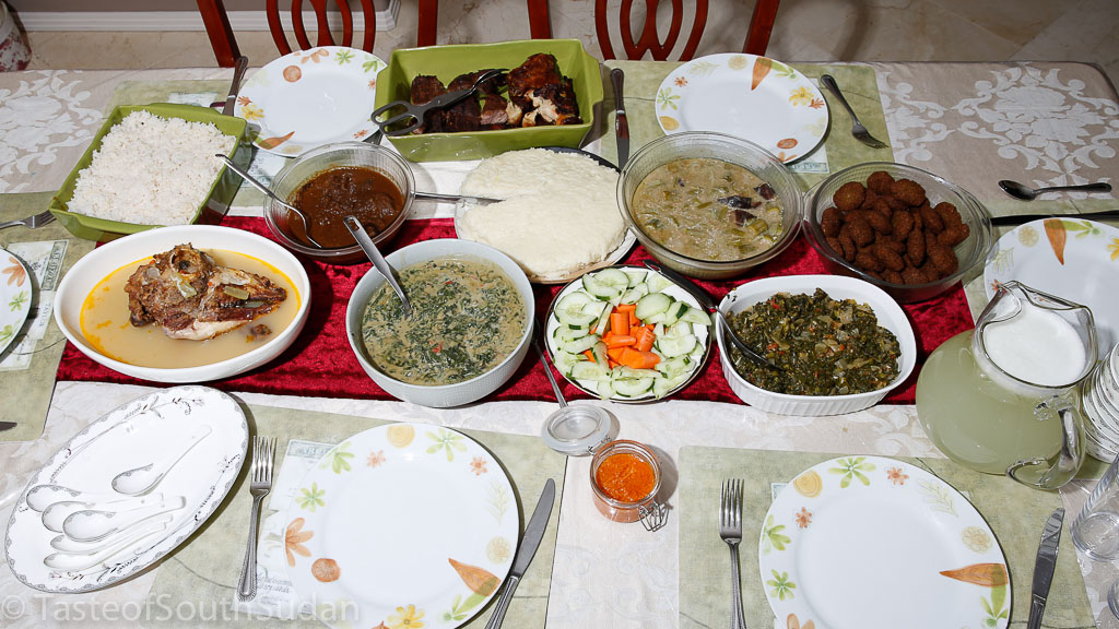 South Sudanese dinner party. Front row: fresh lemonade, Sukuma wiki, cucumber and carrots salad, spinach in peanut butter sauce, lamb head soup, Second row from Right: Rice, Doro Wat (Ethiopian spiced chicken stew), Asida, Smoked meat and okra, Tamiya, Back row: barbecue chicken and steak.