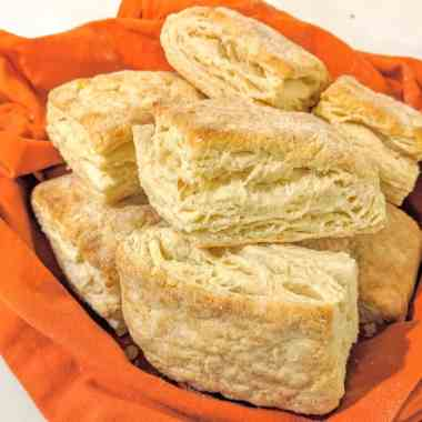 Bowl lined with orange napkin full of made from scratch buttermilk biscuits