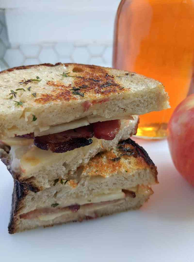 Camembert grilled cheese with bacon, apple, and thyme sitting on a white counter next to a red apple and a large jar of honey in front of a white hexagonal backsplash