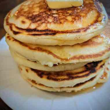 stack of golden buttermilk pancakes on a white plate topped with butter and pure maple syrup