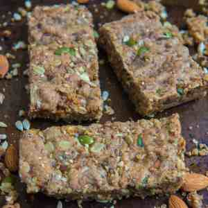 5 seed almond bars on a sheet pan surrounding by almonds and crumbs