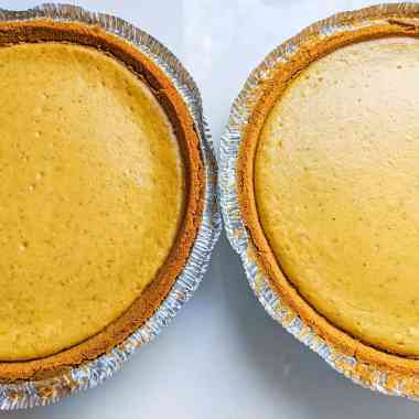 2 cooked pumpkin cheesecakes in premade 9 inch graham cracker crusts sitting on top of white quartz countertop