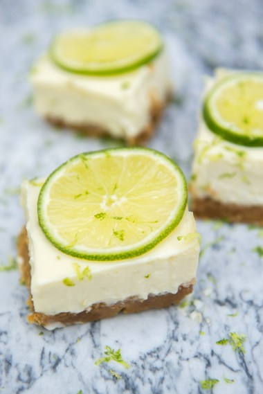 3 key lime pie bars on a marble slab topped with lime slices and lime zest