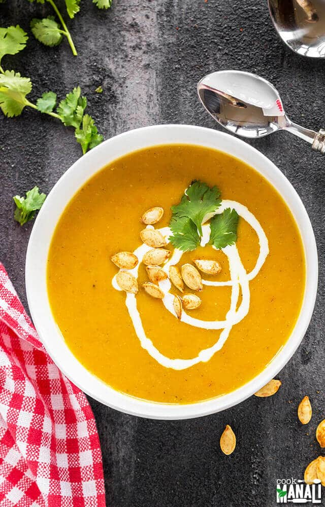 bowl of creamy vegan soup made with pumpkin, carrots and apples
