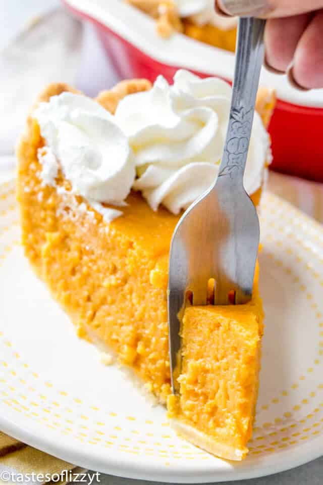 a slice of homemade sweet potato pie with a fork cutting into it